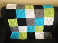 Bright, colorful and soft crochet baby blanket in neon green, gray, white, blue and black
