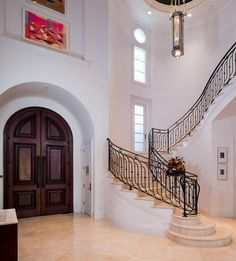 Balcony at landing of white marble serpentine staircase...