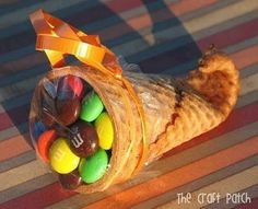 Using a sugar cone, dip the tip in warm water for about 20 seconds then microwave for 20 seconds. Roll the warm, moistened end around a clean pencil and hold for 20 seconds.  Voila...Mini Cornucopias:) Fill with whatever you like, use as a place card... /