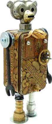 """Name: Bananadanna  D.O.B.: 8/14/11  Height: 12.5""""  Principal Components: Mixed nuts tin, sprinkler head, wrenches, oil lamp burner, clock gear, spring, hydraulic fittings, brooch, erector set curved girder (tail)"""