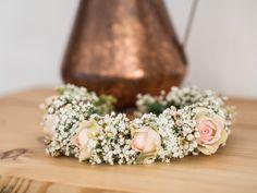 Ein Kranz aus rosa Rosen und Schleierkraut als Braut-Haarschmuck