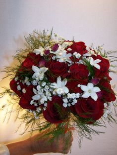 Dark red and white wedding bouquet. This bouquet includes Red Roses, Stephanotis, and babies breath. Hand tied for a beautiful winter wedding, but would look great anytime of the year!