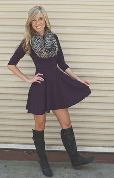 Solid-colored dress, patterned infinity scarf with tall black boots.