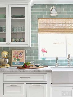 Subway tiles in seafoam green instead of the usual white give the kitchen a color kick. Run to the ceiling, the smooth, glossy tiles also provide a textural changeup from all the wood. Bright white cabinetry with traditional recessed panels supplies plenty of neutral color to the fresh palette.