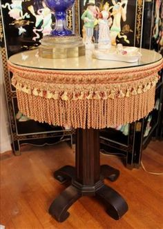 Found on EstateSales.NET: 81 - Mahogany Empire round center table, upholstered top with tassels, ca. 1880, 30 in. T, 24 in. D.