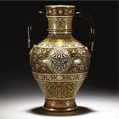 A J.  L. LOBMEYR ENAMELLED 'PERSIAN-STYLE' TWO-HANDLED GLASS VASE VIENNA, CIRCA 1878 the ovoid form of amber-tint, with flared neck and gilt collar, two loop handles and waisted base, painted with panels of geometric scroll within panels of flowers, heightened in gilding