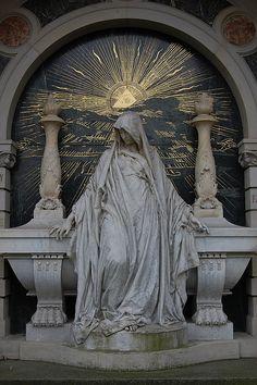 Woman sitting on grave, Illuminati sun    Seen at cemetery in Berlin, Alter Sankt Matthaeus Kirchhof