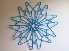 Wall decoration made with plastic hangers.  Could spray in metallic paint to make hanging Christmas stars.
