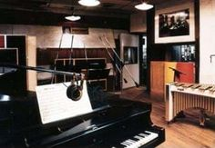 Photo shows a room with a piano, instruments and microphones in the foreground along with other musical instruments.