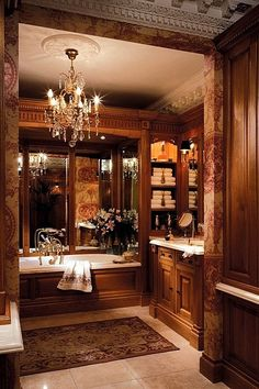 #LuxuryBath, #MasterBath Old World Style with wood paneled walls and tub. Large Mirror behind tub makes the space look larger. #EuropeanStyleHome.  Classical mouldings.  Great built-in shelves for towels. Would your man love this bath?