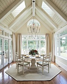 You are surrounded by light in this dining room by Carolina Design Associates. I love the painted wood vaulted ceiling with skylights and the French doors to the adjoining terrace... V
