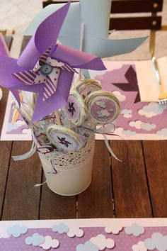 Lollipops and paper windmills in a white flowerpot. Windmills made by hand by using different type of craft papers and little blue buttons. Creative handmade design solutions for babyshower events.