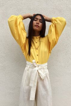 It's time we welcome back the effortless beauty of a fancy blouse into our wardrobes. Consider the blouson top from OR, the cool in-house label of Los Angeles boutique Mixed Business. With its voluminous sleeves, band collar and refreshing, dandelion yellow poplin, this pretty button up could be the best styling trick up our pintucked sleeves this fall.