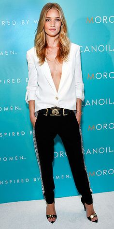 The supermodel takes the plunge in a revealing white blazer and black pants (which boast patterned side panels) by ...
