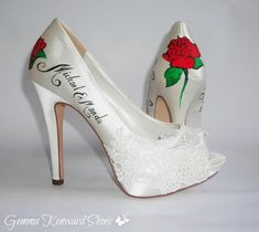 Red roses painted on a pair of white satin and lace wedding shoes.