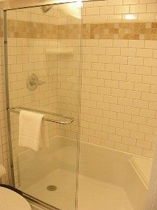 Shower: Note combination of tile on walls with fiberglass/acrylic solid surface base (built in bench)...glass doors.