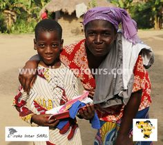 happy child and mother in village in Benin. Happy because of the schoolstuff and clothes for present.