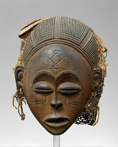 Mask: Female (Pwo). Metropolitan Museum info on their Female (Pwo) mask. Chokwe peoples (Democratic Republic of the Congo). Late 19th to early 20th century C.E. Wood, fiber, pigment, and metal.