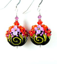 Handmade colorful floral dangle earrings featuring red, orange, purple, green and black floral artisan crafted lampwork beads; sterling silver; Amethyst AB and Light Siam Satin Swarovski crystals.  These gorgeous earrings are composed of beautifully detailed, 22 mm lampwork lentil beads created by an SRA lampwork artist. The beads are black with red, purple and orange flowers, purple buds and green leaves. Amethyst AB and Light Siam Satin Swarovski crystals compliment the beads and add…