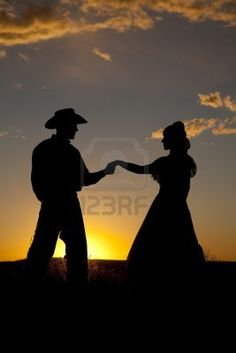 A cowboy couple is silhouetted in the sunset and holding hands.