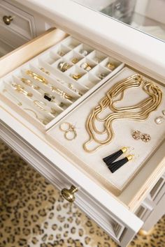 Gold jewelry is perfectly organized in blogger Rachel Parcell's walk in closet thanks to the white drawer organizers.