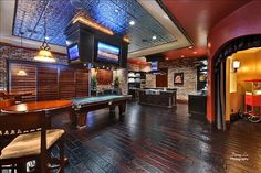 Neat rec room with the bar and kitchen in the background. Cool theater entrance too.