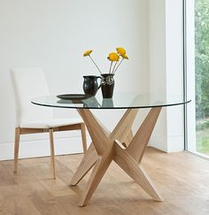 This dining table its unique character. It has a 1200mm diameter circular oak veneered or wenge stained tabletop that has solid, tapered edge. A 10 mm thick toughened glass top is also available. The base is intricately constructed from two interlocking pieces, which gives the piece a sculptural feel which can comfortably fit 6 people.