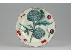 A Chelsea botanical plate, painted in the Hans Sloane style with two large artichokes surrounded by fruit, red anchor mark. Broken into five pieces and repaired. c.1755-60, 21.5cm.