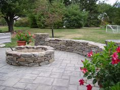 A natural field-stone fire feature with a free standing natural field stone seat wall. Designed and installed by eichenlaub.