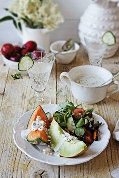Melon salad with plums, green leaves, cucumber, seafood, feta and lemon, mint, yogurt sauce