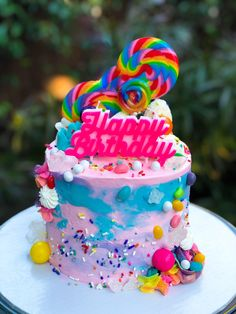 Rainbow overloaded birthday cake with candy and lollipops. #colorful #colorfulbirthdaycake #rainbowbirthdaycake #overloadedbirthdaycake #girlbirthdaycakes #teenbirthdaycakes