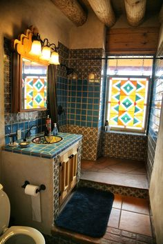 Earthship bathroom inspiration.  Cool Idea to out stain glass window for room with no view outside.