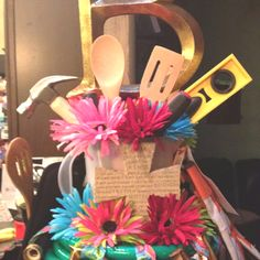 Couples shower centerpiece using garden hose, pitcher. And arrangement made with tools and kitchen utensils.