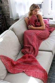 Chica recostada en un sofá mientras tiene las piernas cubiertas por una frazada…