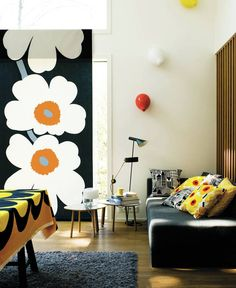 Znak rozpoznawczy fińskiej marki Marimekko – kwiatowy wzór Unikko – zdominował wystrój tego salonu. Tkanina pojawia się nie tylko w oknie, ale też na poduszkach na sofie. Odważnie połączono ją z równie wyrazistym wzorem Kaivo na obrusie.