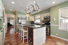 Here's another example of light green wall paint featuring in an open, bright kitchen. Warm, earth tone tiles seat white cabinetry with black countertops.