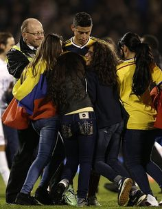 Supporters invade the pitch to celebrate with Colombia's midfielder James Rodriguez (C) after the friendly international football match between United States and Colombia at Craven Cottage in London on November 14, 2014. Colombia won the game 2-1