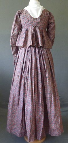 Sold by Meg Andrews, item 7531. c1820s dutch short gown. two piece, roller printed in a red and mid blue squared pattern cotton, probably French, filled with flower heads, some with spotted grounds, the large scoop neck with drawstring, front closure, a straight dart from the horizontal seam below the bust, the long sleeves gathered at the shoulder, slightly flaring at the hands, the back with seams from the shoulders to the centre high back seam, three silk covered buttons above pleating