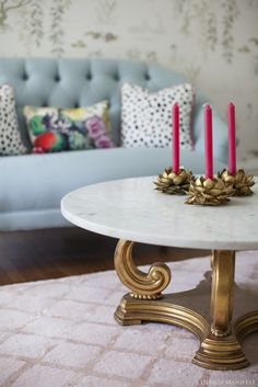 Vintage gold and marble coffee table, lotus candleholders  room by Design Manifest