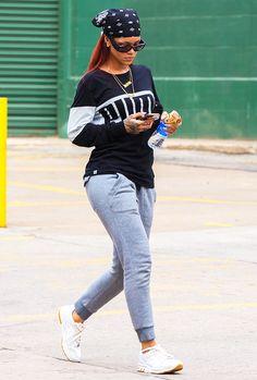 Rihanna wears a Puma sweatshirt, gray sweatpants, a bandana, white sneakers, oversized sunglasses, and gold jewelry