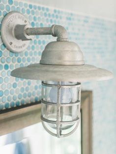 Coastal Influence A maritime style sconce with cage above the bathroom's vanity mirror reinforces the coastal theme and provides illumination for the space.