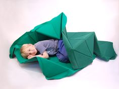 This one is not a tutorial, but is a simple enough concept that I think I could reproduce it - construction quilt was designed as simple multifunctional interior piece that can be transformed into a toy by children. It works as a carpet, a couch cover and can be converted into a landscape for toy cars or fort to play in. it works off of a simple grid of triangles made of dense foam covered with wool felt.