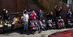 Young children from Teddies Nursery wave to Lizzy from their pushchairs at Riverhead