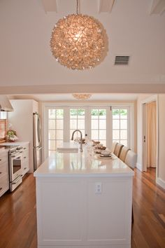 Blair Gordon DesignLovely kitchen design with Viva Terra Lotus Flower Chandelier, white kitchen island with white quartz countertop and French doors.