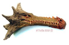 """""""From Days Past""""     20 inches long and 12 inches at his tallest point.  This dragon is carved from a piece of Port Orford   Cedar driftwood. His muzzle is the trunk of the tree  and the back of his head is what's left of the roots.  I've added just a touch of color using thinned oil paints.  Signed and dated:   N. Tuttle 7/15/15 Wood Carving Faces, Wood Carving Art, Wood Carvings, Driftwood Signs, Driftwood Crafts, Driftwood Furniture, Fish Tank Terrarium, Aquarium Fish Tank, Wood Sculpture"""
