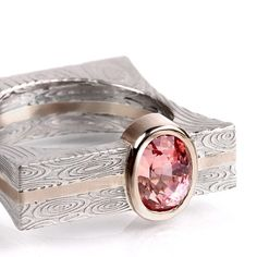 Padparadscha sapphire ring in Damascus and 18k Palladium white gold. By Chris Ploof.