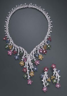 A SPECTACULAR SUITE OF MULTI-GEM JEWELRY Comprising a necklace of flexible design, composed of a series of graduated pavé-set diamond links, the front enhanced by oval-cut sapphire, pink sapphire, yellow sapphire, ruby and tsavorite garnet and circular-cut diamond flowers; and a pair of ear pendants en suite, mounted in 18k white and oxidized white gold, necklace 15 ins.