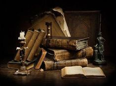 Old antique books by candle light and an old hourglass timer