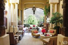 Will and Jada Pinkett Smith's California living room includes a 1930s copper lantern from Downtown, columns wrapped in jute rope, a pair of '60s Brazilian rosewood chairs (at left) from Noho Modern, custom-made lounge seating (at right) upholstered in a Rose Tarlow leather, wing chairs covered in kilims and leather, and a beige silk area rug by Hokanson.