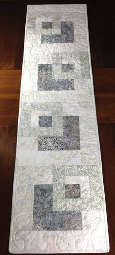 Modern Batik Table Runner, Handmade Gray Quilted Tablerunner, Grey Wallhanging, Reversible Table Quilt, Contemporary Dining Room Decor ----------------------------------------- Although designed as a modern look table runner, this quilt could also be used to adorn your wall, a dresser, coffee table, sofa table, buffet, desk, bed or piano top. The neutral gray color scheme is versatile and can be used in any season. A layer of batting enclosed between two layers of cotton fabrics gives extra…